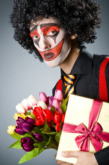Sad clown with the flowers