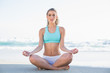 Peaceful slender blonde in sportswear meditating