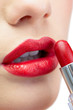 Extreme close up on glamorous model applying red lipstick