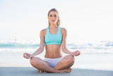Peaceful slender blonde in sportswear meditating