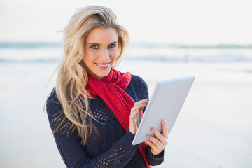 Smiling sexy blonde holding tablet computer