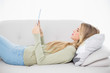 Happy pretty blonde using her tablet lying on cosy sofa