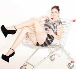 junge Frau sitzt im Einkaufswagen
