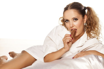 pretty girl in a white shirt lying on a bed and eating chocolate