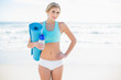 Cheerful blonde woman in sportswear carrying a bottle and an exe