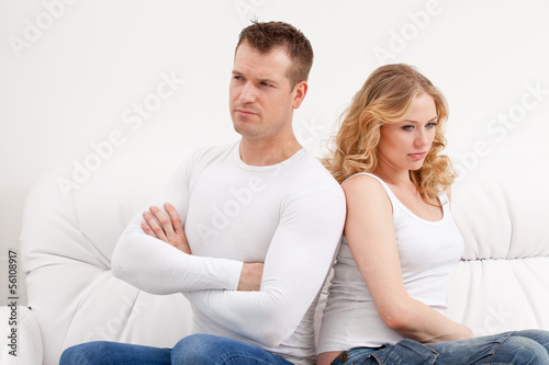 Young sad couple sitting