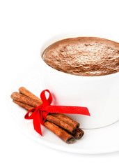 Cup of Hot Christmas Chocolate with cinnamon sticks and red chri