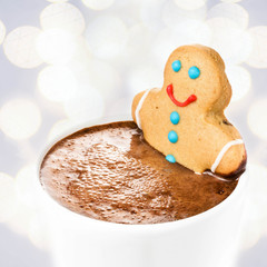 Gingerbread cookie man take a bath in cup of Hot Chocolate, over