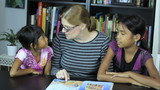 Homeschool Mom Reading To Asian Daughters During School