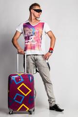 Junger Mann mit Sonnenbrille und Koffer