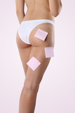 Bum and legs of slim woman over pink background with post it poster