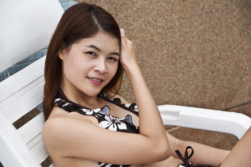 Beautiful Asian woman on poolside chair.