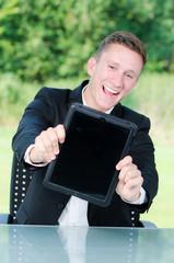 junger mann zeigt begeistert touchpad
