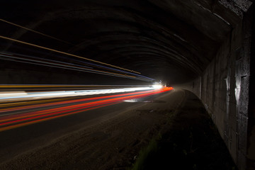 Truck light trails in tunnel.