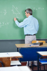 Professor Solving Mathematics On Greenboard In Classroom