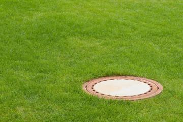 Der Deckel von einem Kanal in einem kräftig grünem Rasen