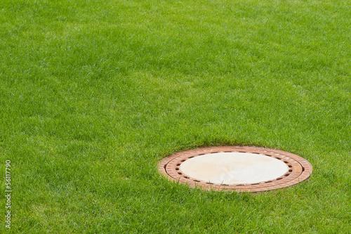 canvas print picture Der Deckel von einem Kanal in einem kräftig grünem Rasen