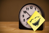 Post-it note with smiley face sticked on clock