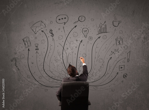 Businessman in front of a chalkboard deciding with arrows and si