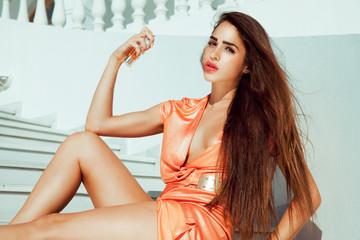 sensual woman holding perfume.