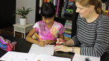 Homeschool Mom Teaching Spelling Lesson To Asian Daughter