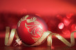 Red xmas ball with golden ribbon on red blurred background