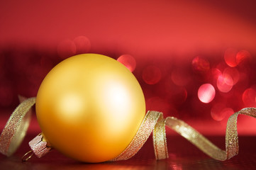 Golden xmas ball and ribbon on the red