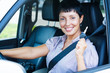 Senior woman holding car key and smiling to you from a car
