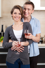 Couple with goblets embraces one another in the kitchen