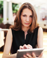 Image of young woman with tablet computer in cafe