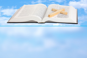 Holy Bible and wooden cross on sky background