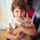 Portrait of cute toddler child girl with baby dog pet.