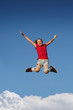 Happy girl jumping over blue sky background