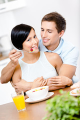 Man feeds and embraces his girlfriend