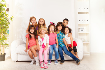 Group of happy hugging kids at home
