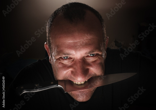Scary man with knife in mouth