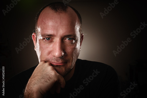Dramatic low-key portrait of adult man looking in camera