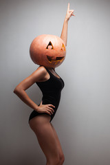 Dancing pretty woman with pumpkin on head