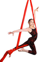 acrobatic young girl exercising on red fabric rope