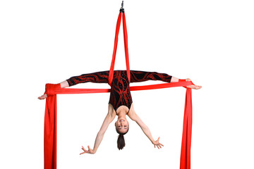 acrobatic girl exercising on red fabric rope