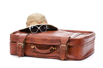 Close up of brown suitcase and straw hat with glasses