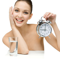 Naked girl with glass of water shows alarm clock