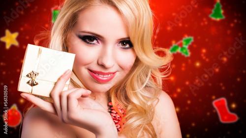 junge blonde Frau mit Geschenk vor weihnachtlichem Hintergrund