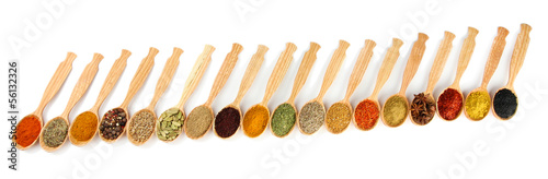 Assortment of spices in wooden spoons, isolated on white