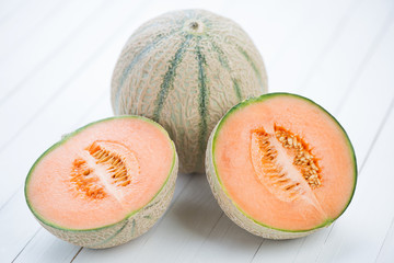 Whole and halved cantaloupe melons on white wooden background