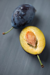 Vertical shot of whole and halved plums, grey wooden background