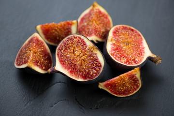 Sliced ripe figs on black wooden background, horizontal shot
