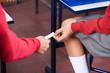 Teenage Girl And Boy Passing Cheat Sheet At Desk