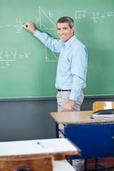 Portrait Of Mature Teacher Writing On Board