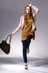 full length Slim young girl with bag posing on light background